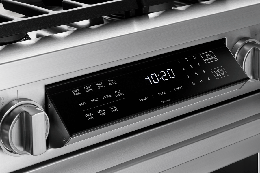 LCD touch screen and knobs on a silver stainless steel Dacor range.