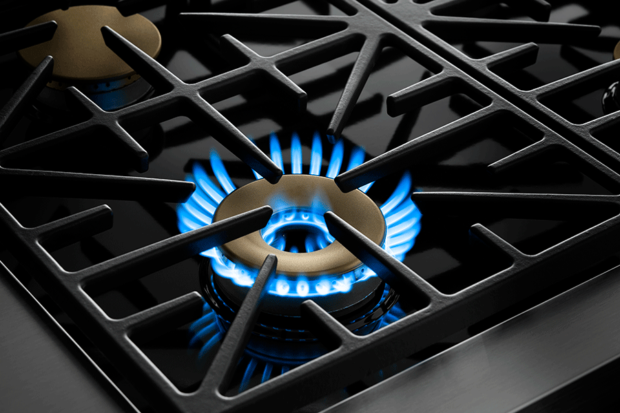 Black grates and gold burners of a Dacor rangetop, with the burner ignited.