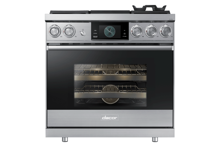 A silver stainless steel Dacor oven range with the oven lights on.