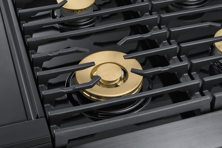 Black grates and gold burners on a Dacor range.