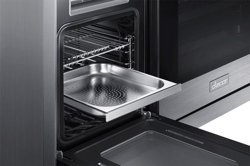 The RealSteam compartment of a Dacor 48 inch contemporary style dual fuel steam range open with the rack pulled out.