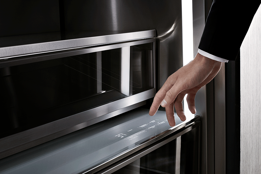 A person using the touch control panel on a Dacor column refrigerator.