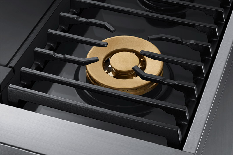 Black grate and gold burner of a Dacor contemporary style 36 inch gas range.