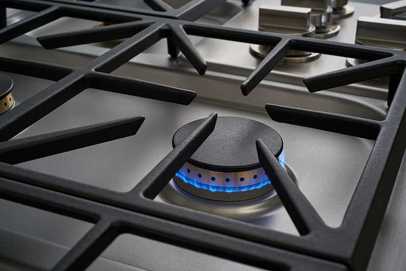 Black grate and burner of a Dacor professional style 36 inch gas cooktop.