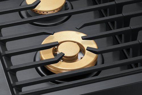Black grates and gold burners of a Dacor contemporary style 30 inch gas cooktop.