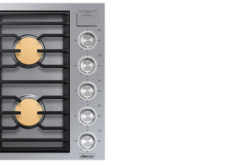 The control knobs of a silver stainless steel Dacor contemporary style 36 inch gas cooktop.