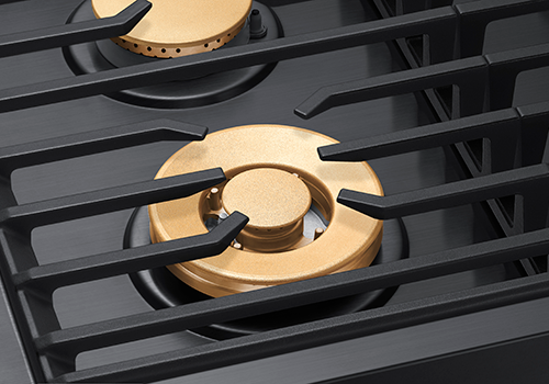 Black grates and gold burners of a Dacor contemporary style 36 inch gas cooktop.