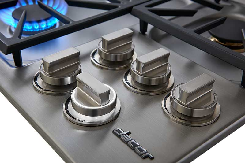The knobs of a silver stainless steel Dacor professional style 36 inch gas cooktop.
