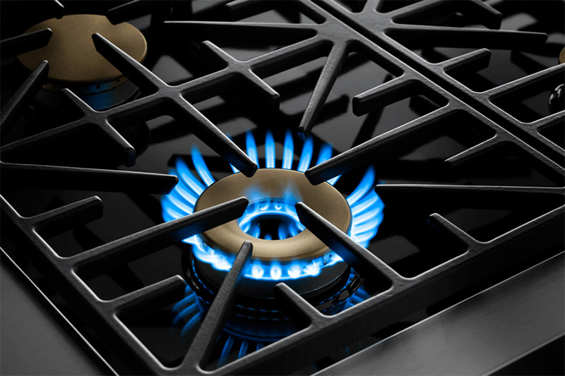 Black grates and gold burners of a Dacor professional style 36 inch dual-fuel range, with the burner ignited.